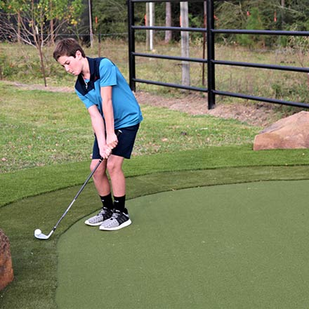 Boy playing golf on SYNLawn Artificial Turf