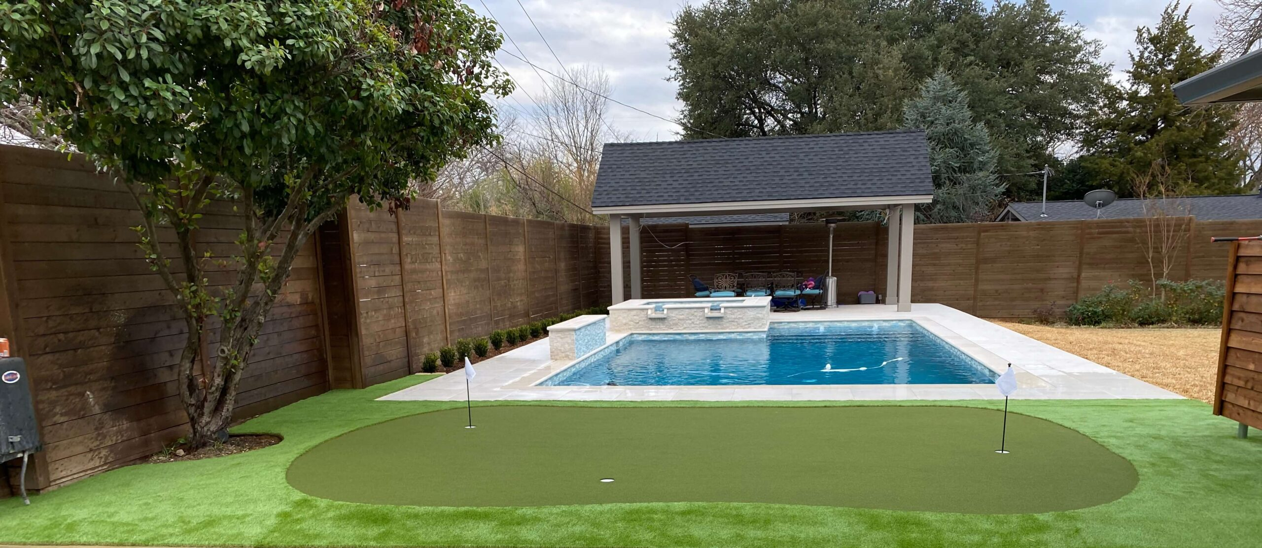 backyard with artificial turf and putting green